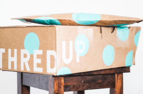 Mint green Polkadot ThredUp boxes stacked on a table before being opened