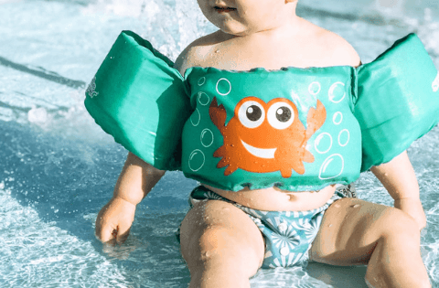 Toddler sitting in water wearing a green puddle jumper and swim diaper.