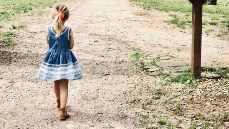 A toddler girl walking on a dirt road in a blue denim dress