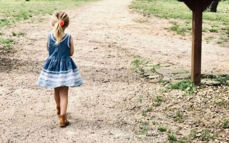 A toddler girl walking on a dirt road in a blue denim dress