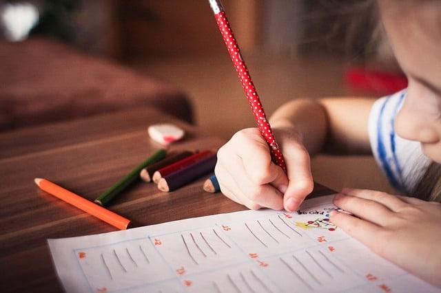 kindergarten homeschooler writing on a piece of paper