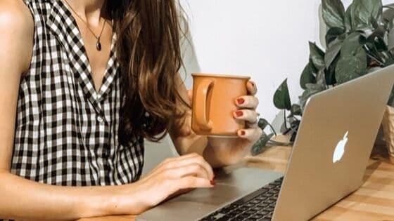 a woman holding a coffee mug while working on a mac computer