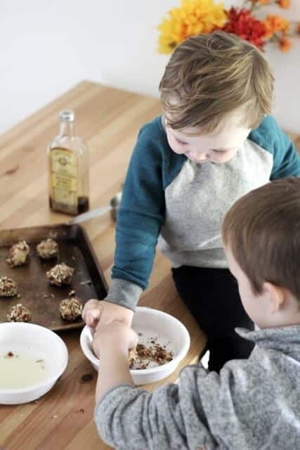 kids rolling thumbprint cookies in egg whites and chopped pecans