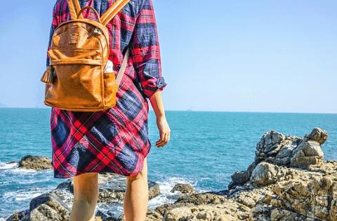 cognac diaper packpack on a girl by the ocean