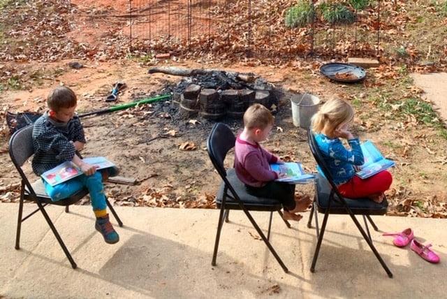 a kindergarten boy reading outside for homeschool