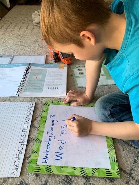 a kindergarten boy writing the date