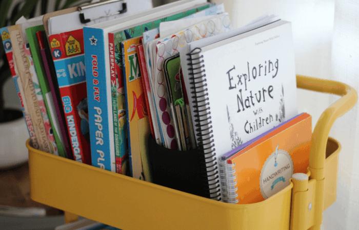 homeschool kindergarten books in a metal cart