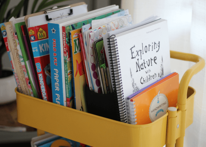 homeschool kindergarten books in a metal cart