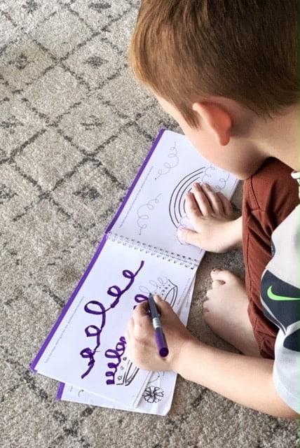 a kindergarten boy working on pre writing workbook tracing swirls and loops