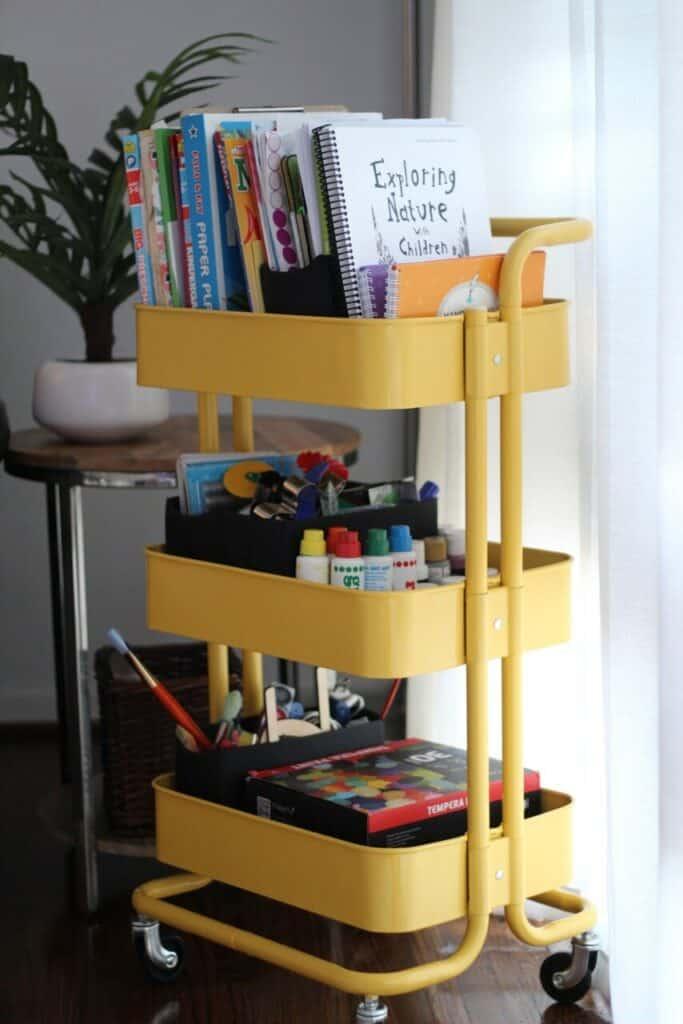 metal yellow cart on wheels holding homeschool supplies