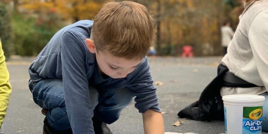kindergarten boy rolling out clay outside