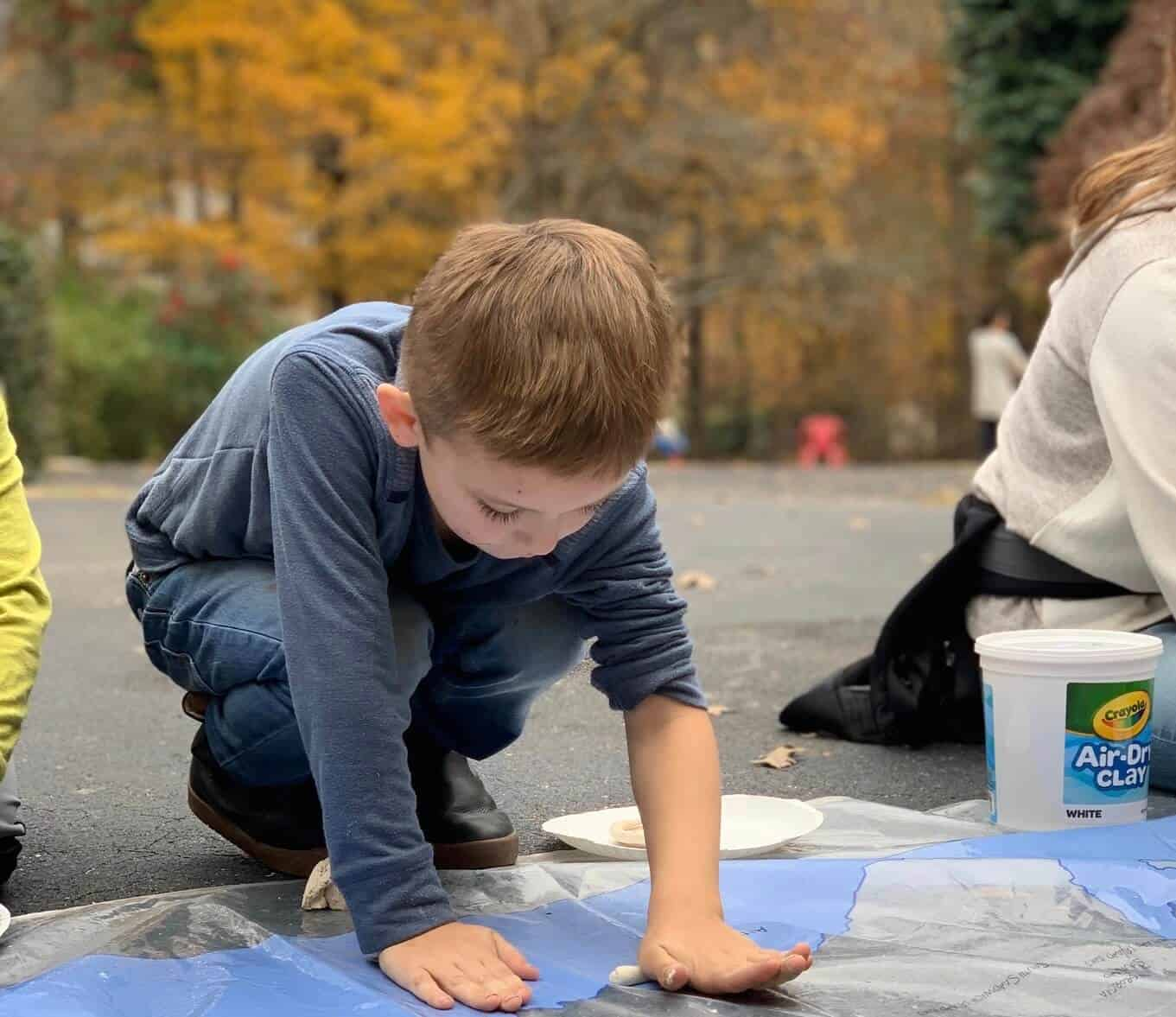 kindergarten boy rolling out clay outside