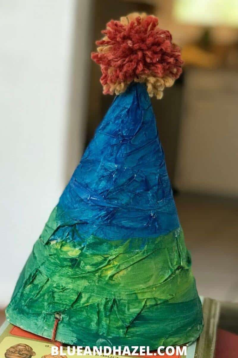 homemade birthday party hat painted blue and green, with an orange yarn ball on top