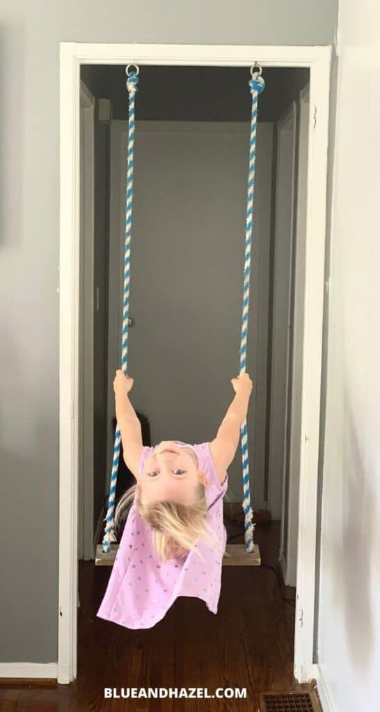 A little girl swinging on an indoor swing made of rope and a board.