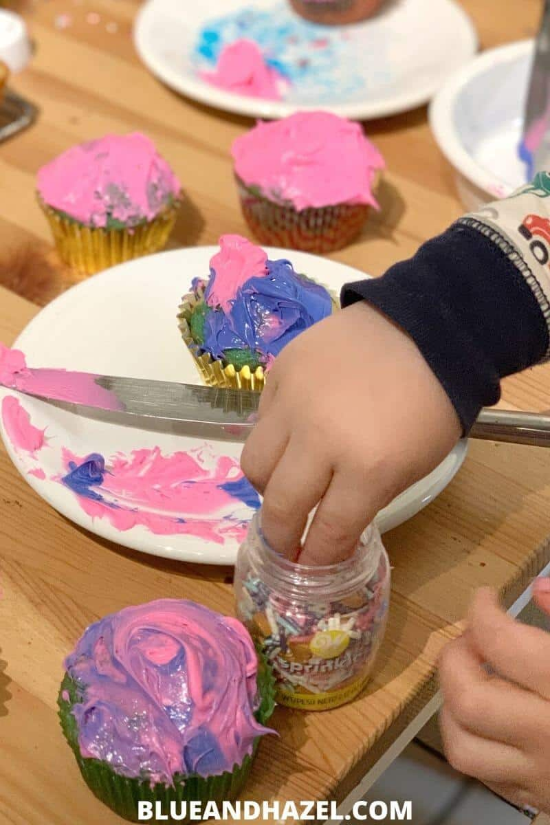 kids decorating cupcakes with pink and purple frosting for a home birthday party