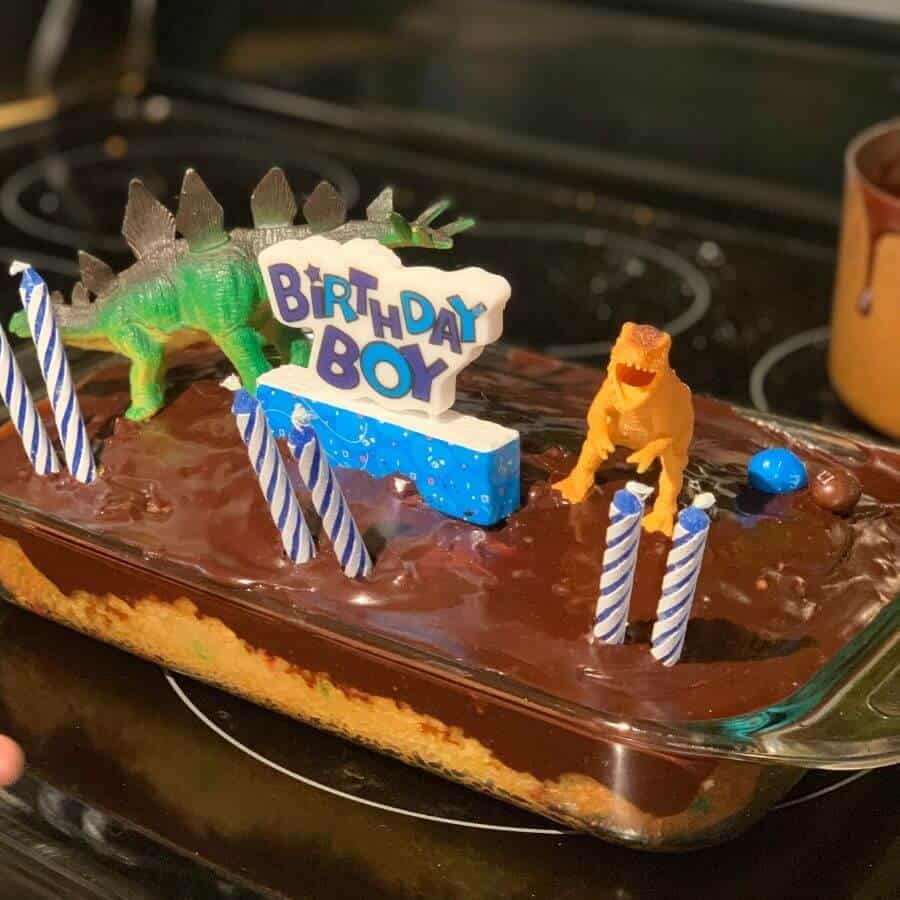 plastic dinosaurs on top of a birthday cake for 6 year old birthday