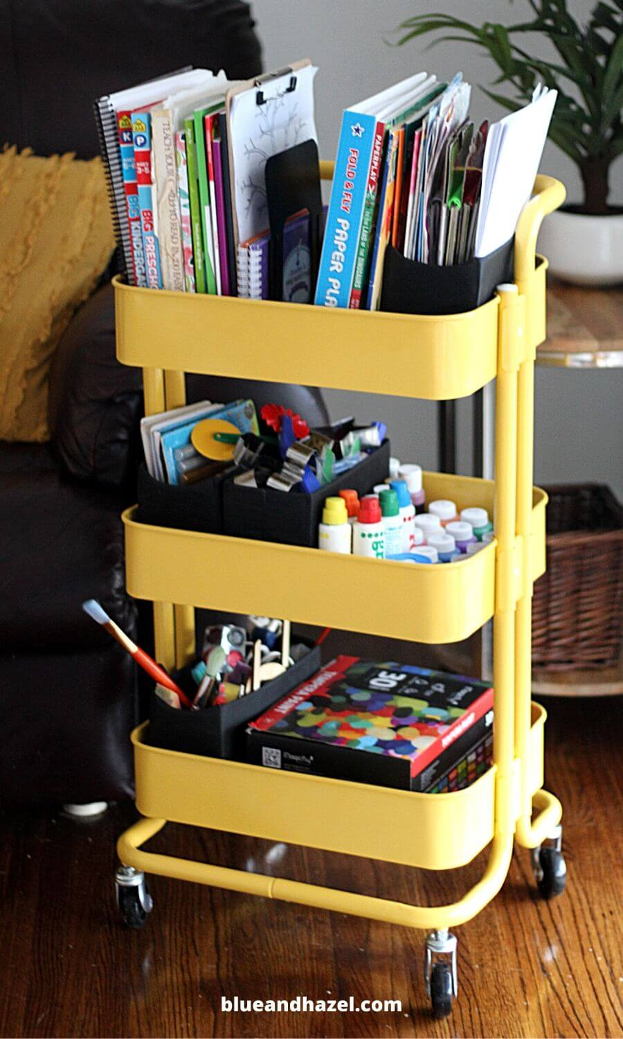 Yellow metal rolling cart used to organize homeschool supplies.