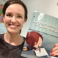 language lessons for a living education level 1 book being held up and reviewed by a homeschool mom