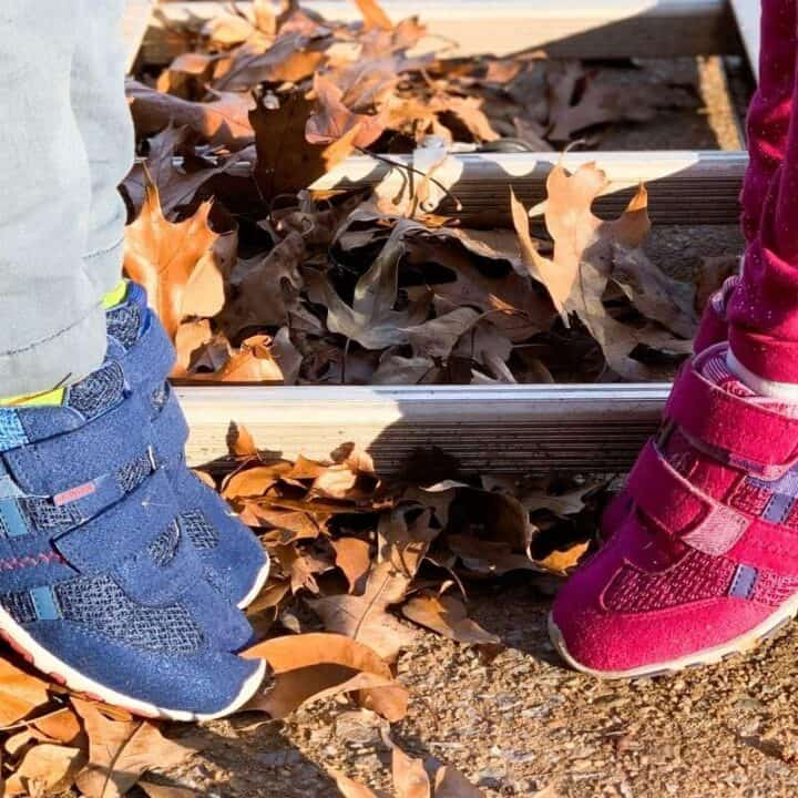 A pink and a blue pair of tennis shoes on two kids standing on a ladder