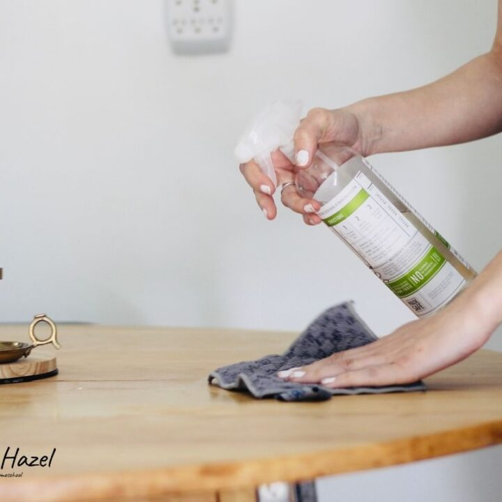 a pregnant woman cleaning a wooden table with Branch Basics all purpose cleaner