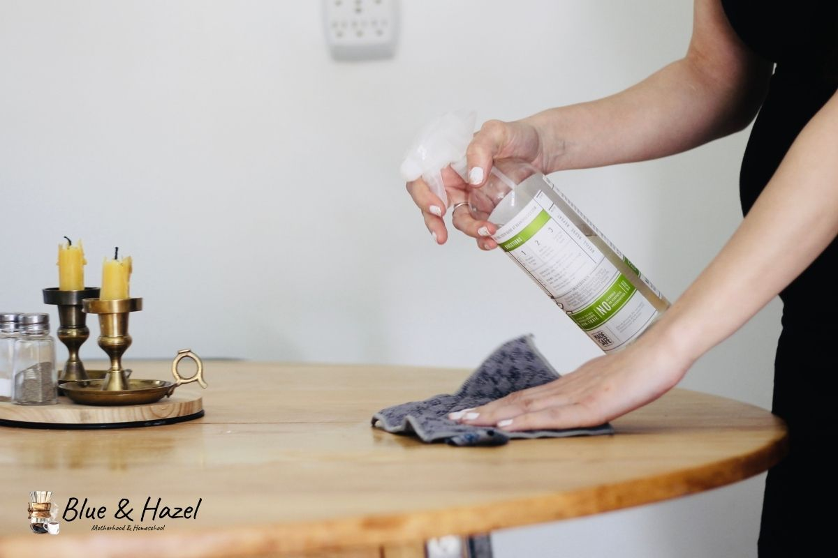 Branch basics all purpose cleaner being sprayed onto a wooden table by a pregnant woman.
