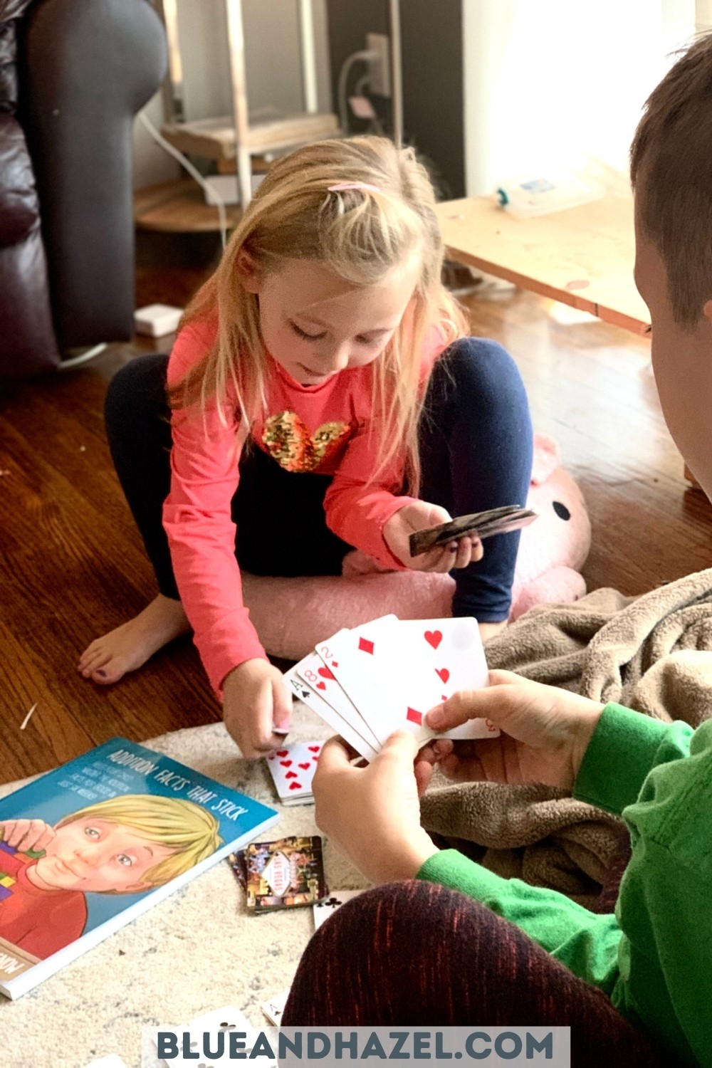 two kids playing card games to learn addition facts.