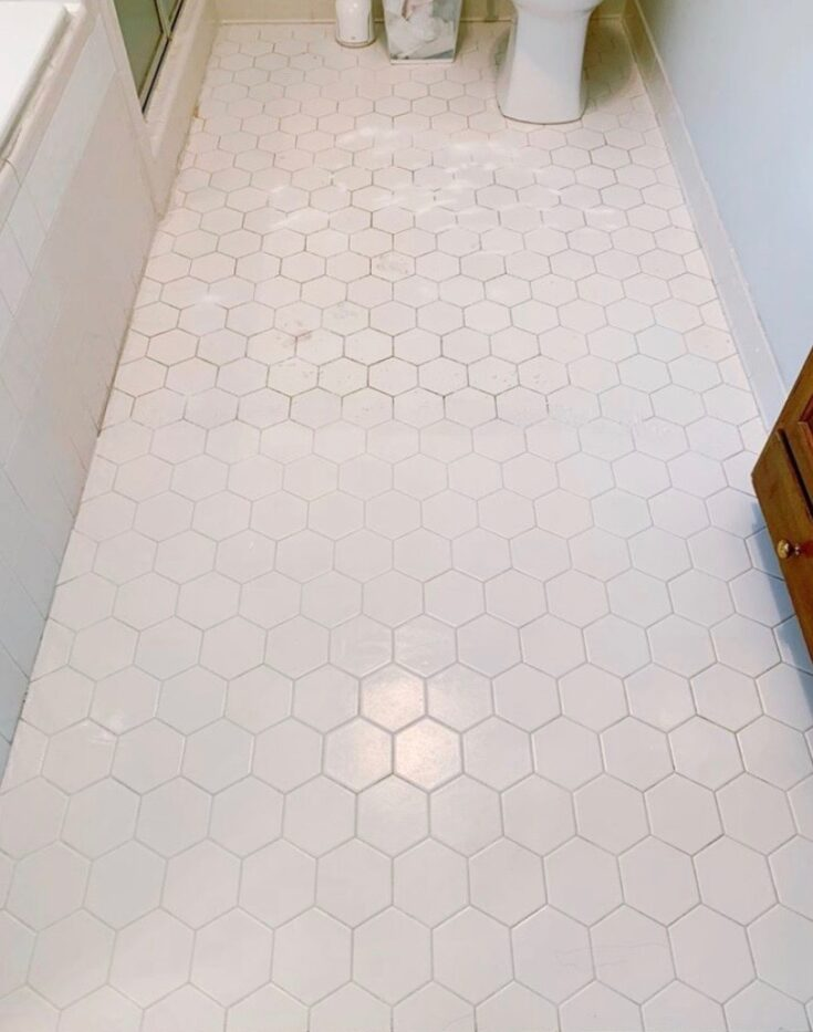 a white tile floor half cleaned using branch basics oxygen boost and bathroom spray. One side is dirty, the other side is white again.