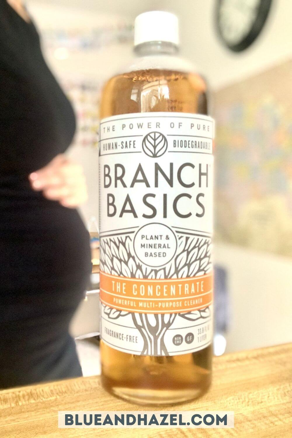 close up of branch basics bottle of concentrate with a pregnant woman standing behind.