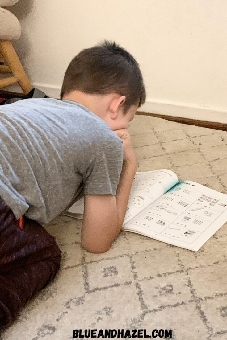 A 1st grade boy completing his homeschool math from the Singapore Math Primary US Edition level 1A.