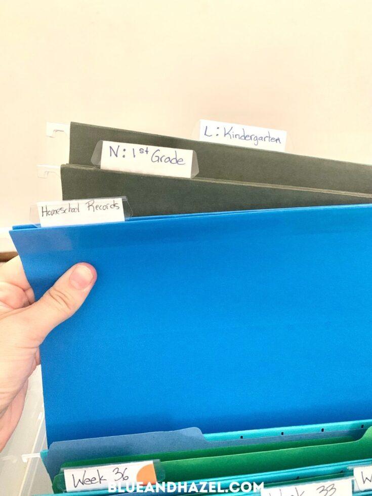 Blue file folders holding homeschool work stored in a clear homeschool crate.