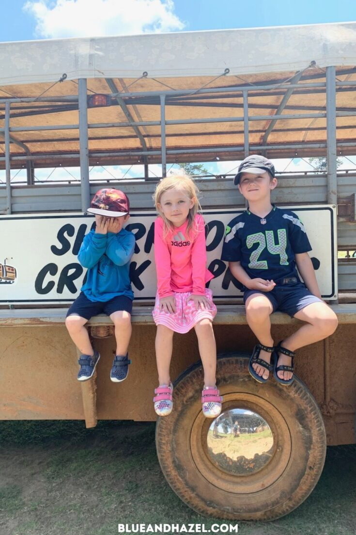 3 kids sitting on the edge of the Shark Tooth Creek Express