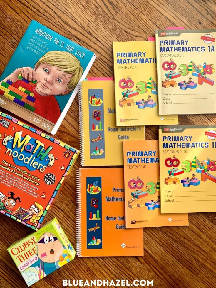 Singapore math 1A & 1B textbook, workbook, and home instructors guide next to the math games clumsy thief and math noodles.