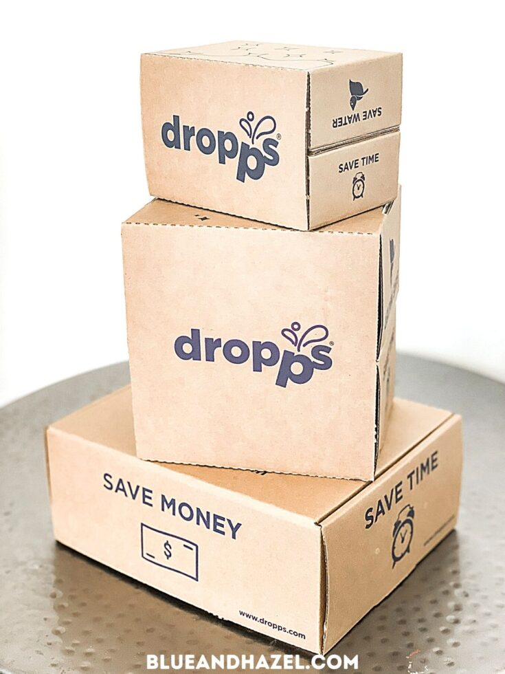 """3 cardboard boxes of Dropps detergent pods delivered in the mail with packaging that says """"save time"""" and """"save money"""""""