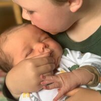 newborn baby held by his big brother