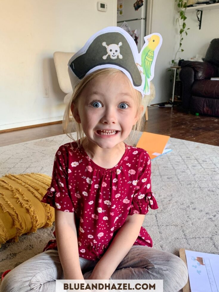 Kindergarten girl smiling wearing a pirate hat made out of paper from a Dash Into Learning activity pack.