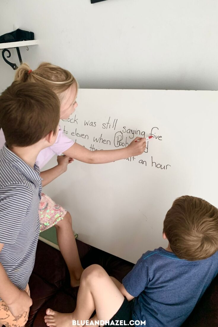 Board work for homeschool language arts. Two young kids circling words in a sentence on a whiteboard.