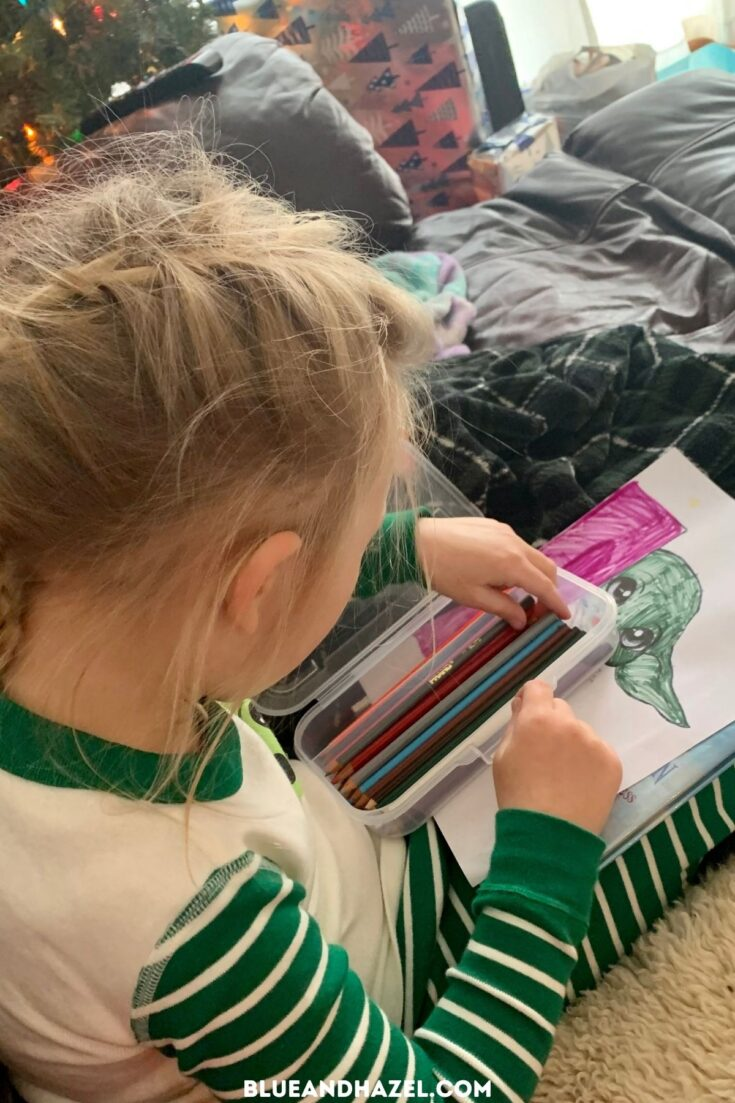 A little girl coloring baby yoda from star wars during quiet time.
