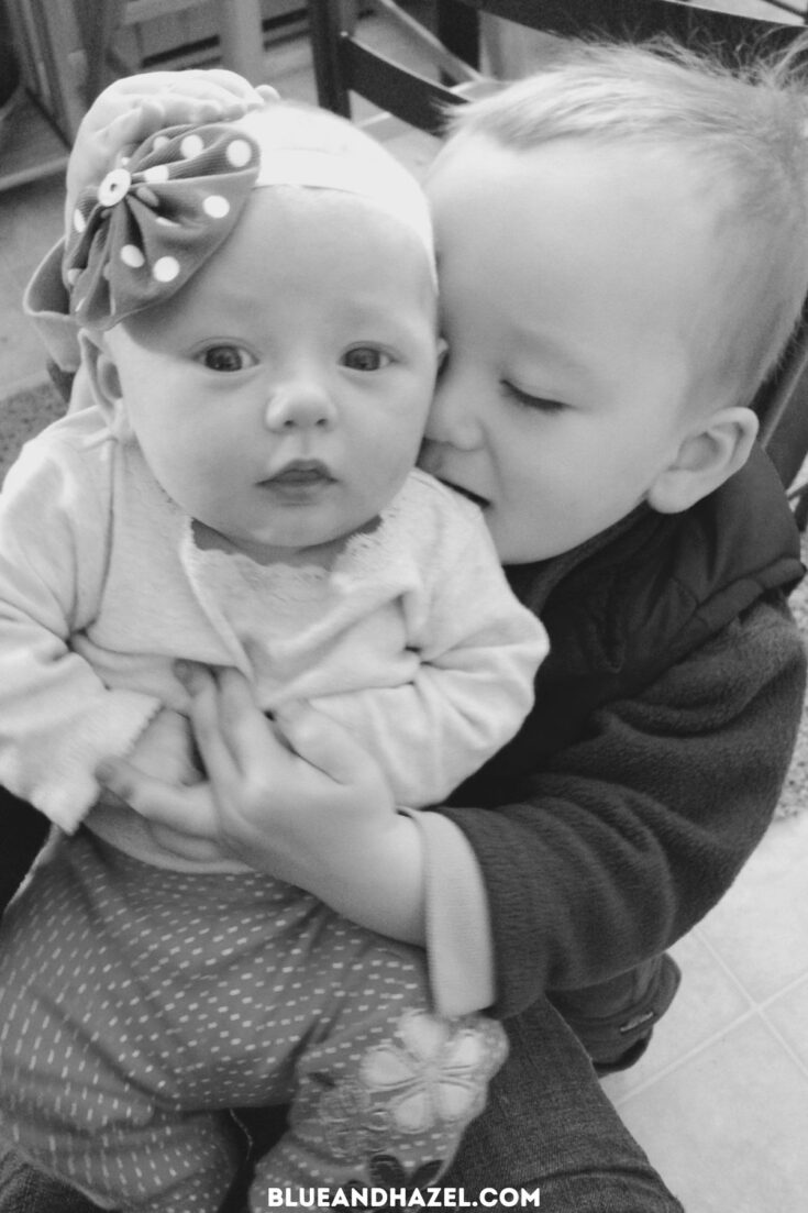 a black and white photo of a newborn baby girl being held by her toddler brother 18 months older.
