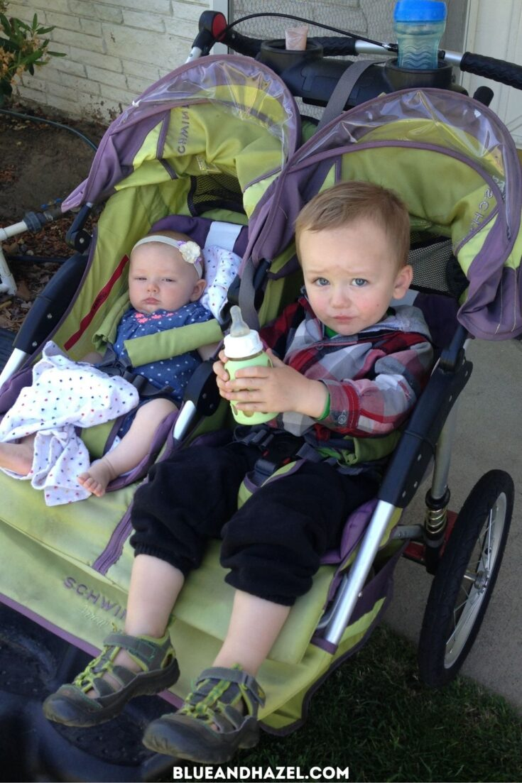 A toddler boy and his newborn sister riding in a green double jogging stroller.